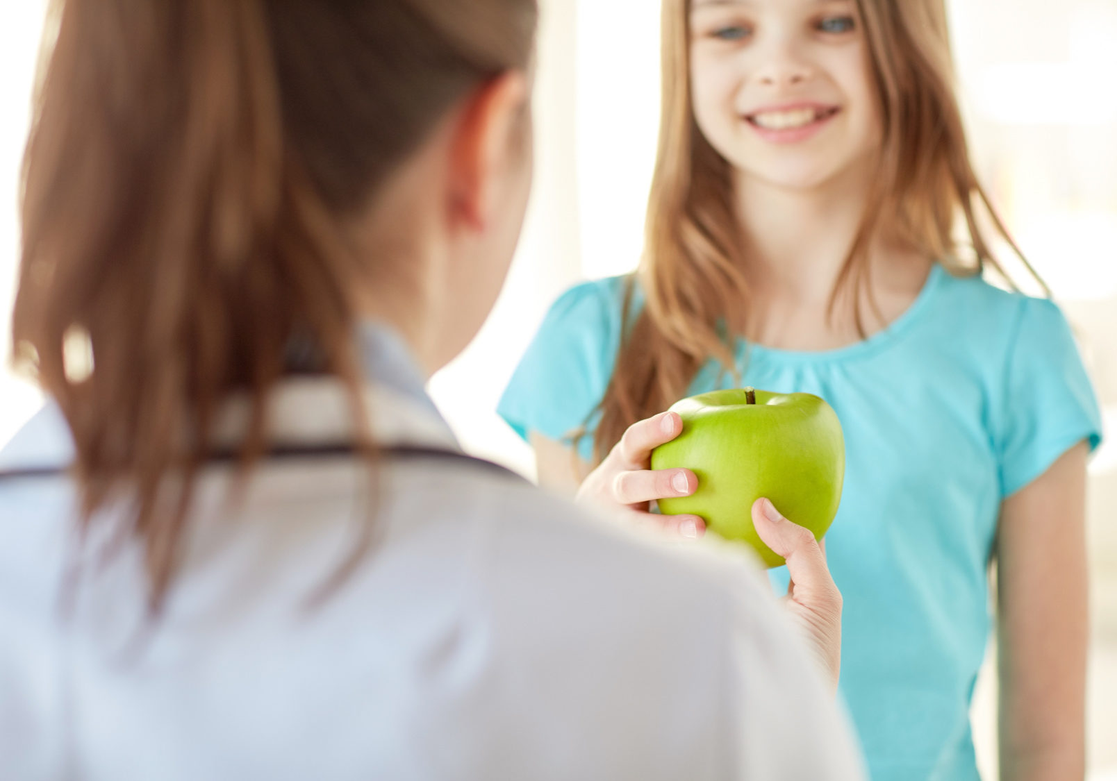 health care, healty eating, people, children and medicine concept - close up of doctor or stomatologist giving green apple to happy girl at hospital